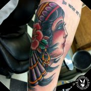 American Traditional Gypsy Girl Tattoo in color with a rose